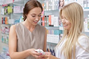 Two shoppers comparing lotion in a pharmacy